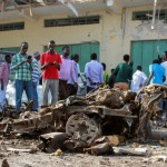 People gather as the remains of an exploded vehicle in Mogadishu, Somalia, on December 19. A resurgence in deadly attacks by the Islamist insurgent group al-Shabaab in recent months has stalled attempts by the citizens of Mogadishu to revive their the city after years of civil war. EPA/SAID YUSUF WARSAME